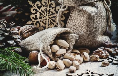 New Year or Christmas composition with walnuts, hazelnuts, pistachios in canvas bags