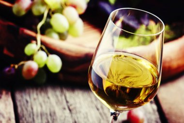 White wine in a glass with fall grapes
