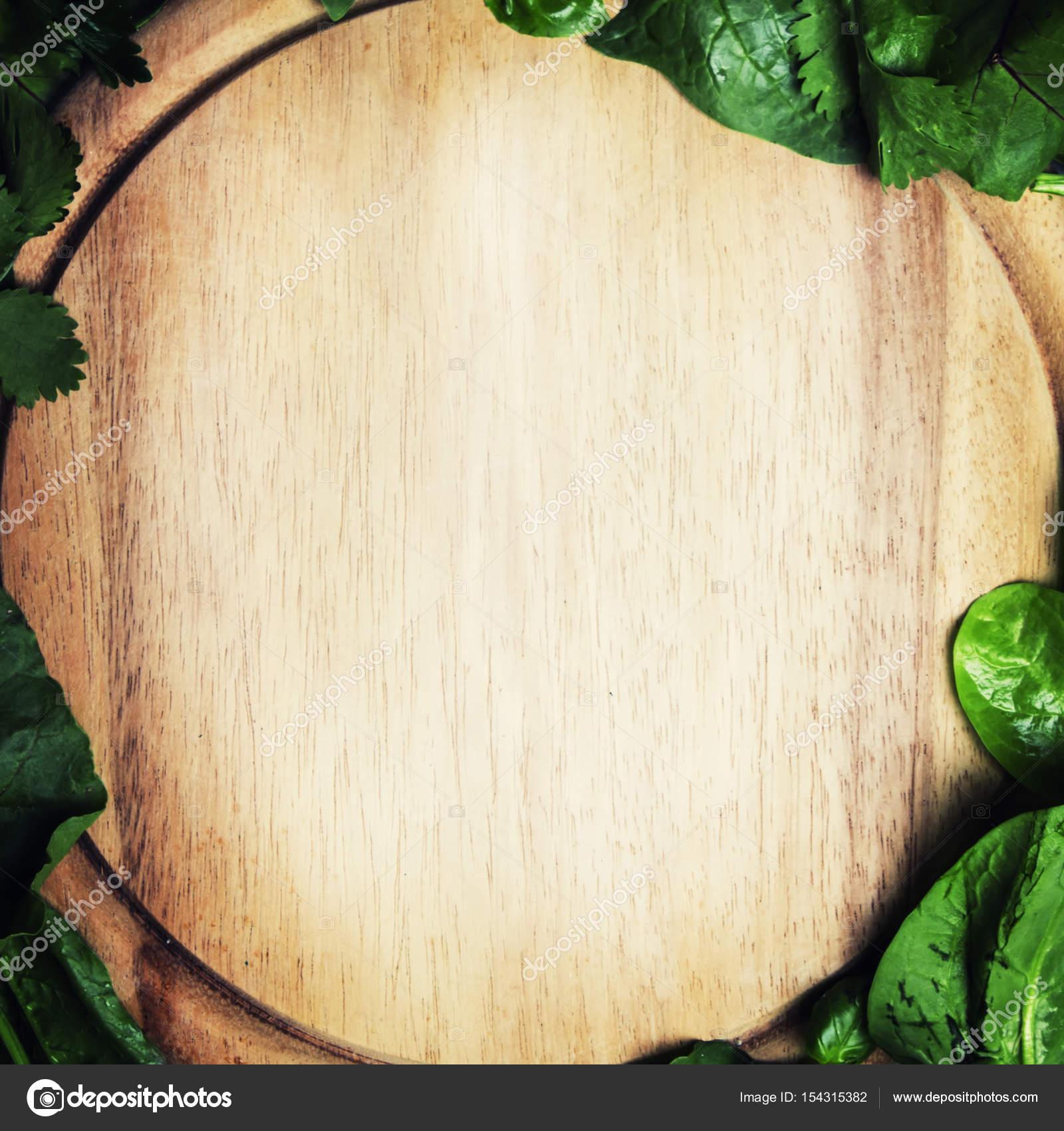 tabla de cortar madera en un marco de hojas verdes — Fotos de Stock ...