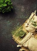 Fotografie Sušenou mátu ve skleněné nádobce a svazek čerstvé máty, medicína byliny na černém pozadí, pohled shora