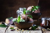 Photo Chocolate ice cream with topping and fried pine nuts decorated with mint leaves, old wooden background, selective focus