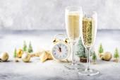 Két pezsgős pohár és karácsonyi dekoráció szürke arany bokeh háttér. Boldog Újévi Ünnepséget! Szelektív fókusz és kis mélységélesség