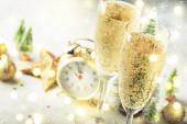 Dvě sklenice šampaňského s pohyblivými bublinkami a vánoční ozdobou na šedém zlatém pozadí bokeh. Šťastnou novoroční oslavu. Selektivní zaměření a malá hloubka pole