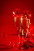 Valentines den červené pozadí s sklenicemi šampaňského, srdce a šarlatové růže, kopírovat prostor