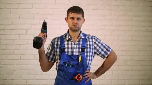 Egy ember egy csavarhúzóval. Dolgozó szerelőt, építő, a munka ruha. Mester kéziszerszámok. Ember rendelkezik a csavarhúzót a kezében. Súlyos munkavállaló egy csavarhúzóval.