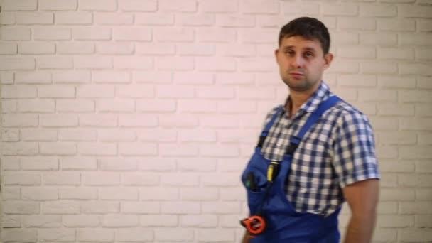 Muž se šroubovákem. Pracovník opravář, tvůrce pracovní oděv. Master elektrické nářadí. Muž, který držel šroubovák v ruce. Pracovník s šroubovák ukazuje palec