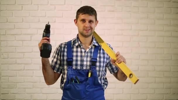 Muž se šroubovákem. Pracovník opravář, tvůrce pracovní oděv. Muž, který držel šroubovák v ruce. Mistr stavební nástroje