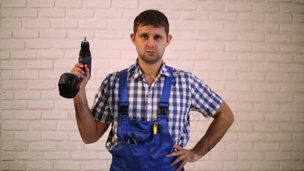 Muž se šroubovákem. Pracovník opravář, tvůrce pracovní oděv. Master elektrické nářadí. Muž, který držel šroubovák v ruce. Vážné pracovní šroubovákem.