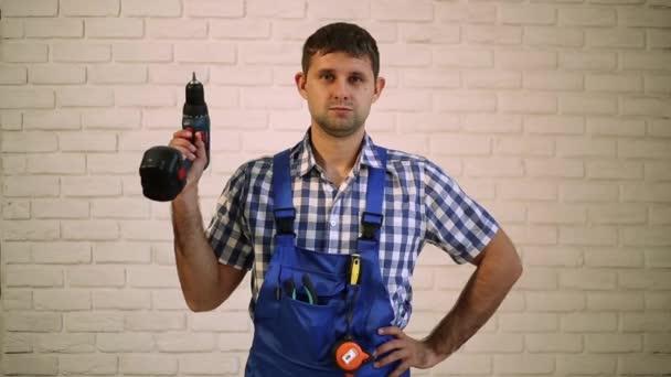 Muž se šroubovákem. Pracovník opravář, tvůrce pracovní oděv. Master elektrické nářadí. Muž, který držel šroubovák v ruce. Pracovník s šroubovák.