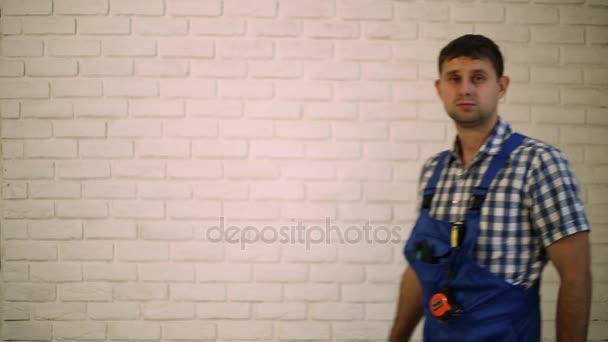 Muž se šroubovákem. Pracovník opravář, tvůrce pracovní oděv. Pracovní nářadí. Muž, který držel šroubováku v ruce