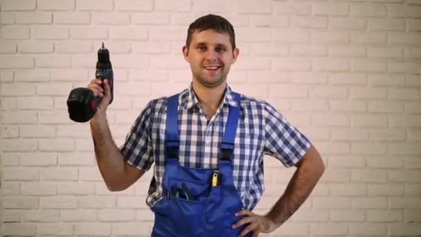 Mann mit einem Schraubenzieher in der Hand. Ein Mann mit einem Schraubenzieher. Arbeiter in der Reparatur, Erbauer des Arbeitsanzugs. Meister der Elektrowerkzeuge.