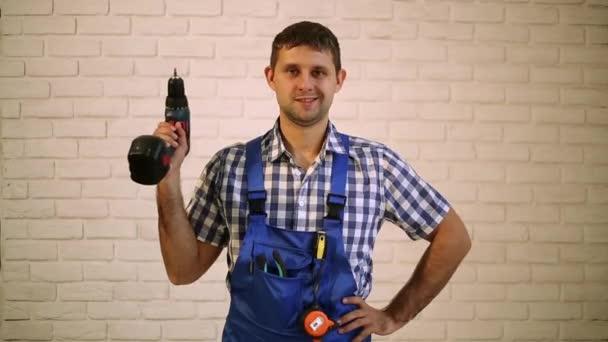 Ein Mann mit einem Schraubenzieher. Arbeiter in der Reparatur, Erbauer des Arbeitsanzugs. Meister der Elektrowerkzeuge.