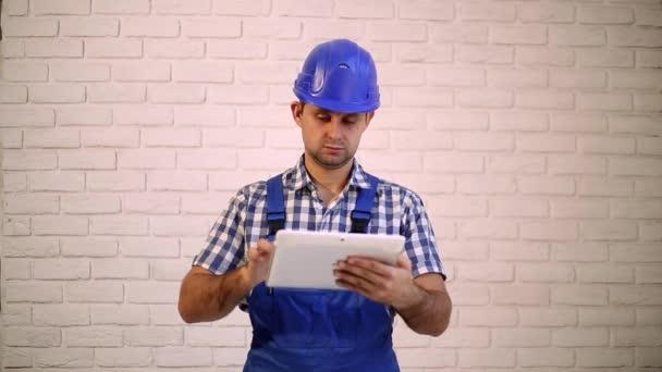 Stavební dělník s tabletovým počítačem. Moderní technika, stavitel, hlavní. Mužské architekt s tabletovým počítačem.