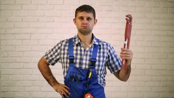 Instalatér s nastavitelným klíčem. Muž drží hlavní domovní instalace. Pracovníka, tvůrce, opravář instalatér na cihlovou zeď na pozadí.