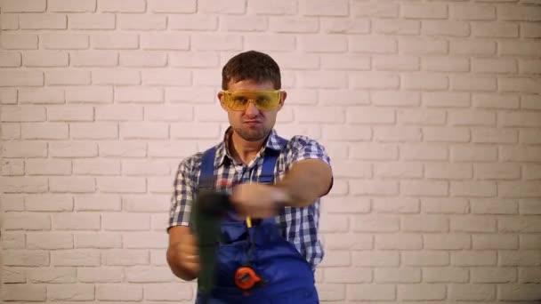Muž s perforační. Práce s vrtačkou. Stavební dělník s kladivem.