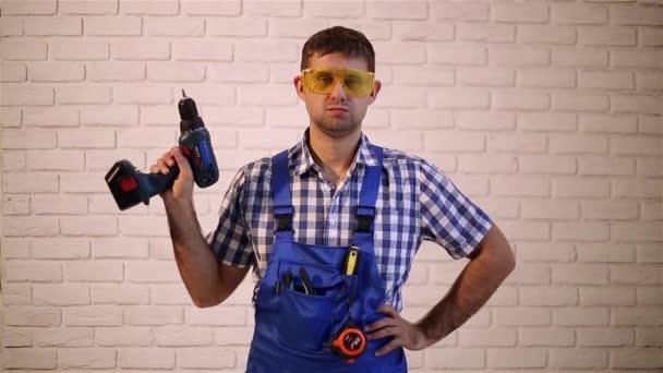 Stavební dělník s šroubovák. Muž s elektrickým nářadím. Muž se šroubovákem. Člověk dělá opravy.
