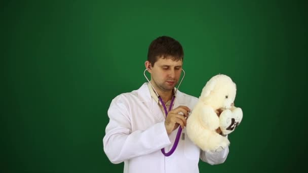 Doctor with a soft toy. Pediatrician, pediatrician on a green background. Doctor listens to a soft toy with a phonendoscope. The doctor heals a teddy bear.
