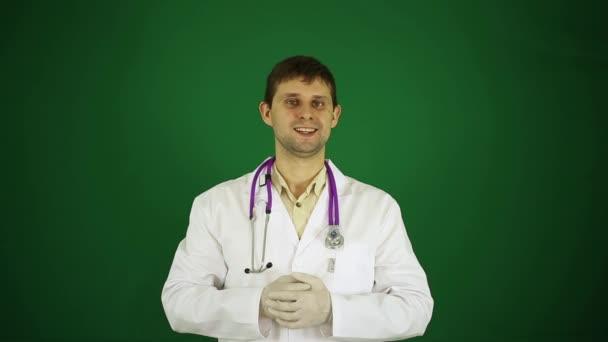Doktor ukazuje prstem na kameru. Lékař na zeleném pozadí. Pozitivní mladý doktor.