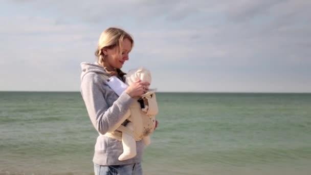 Maminka s dítětem v šátku. Žena s dítětem u moře. Matka s dítětem na pláži. Žena s dítětem venku