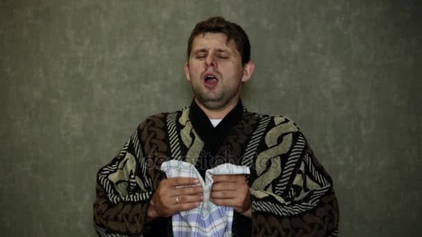 The man has a cold. The man sneezes into his handkerchief.