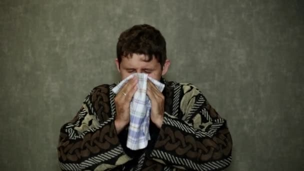 The man sneezes, runny nose, fever. A man in a dressing gown sneezes into his handkerchief.