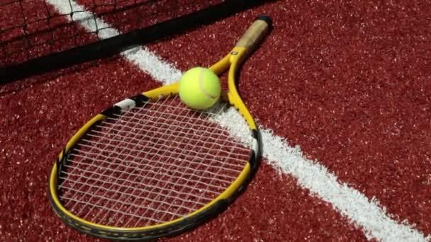 Tenisové rakety a tenisové míčky na kurtu s umělým povrchem. Velký tenis, hry, sport.