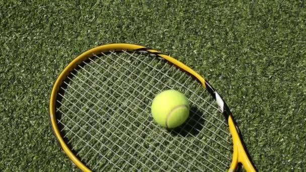 Tenisovou raketu a míček na travnaté hřiště. Tenis a sport.