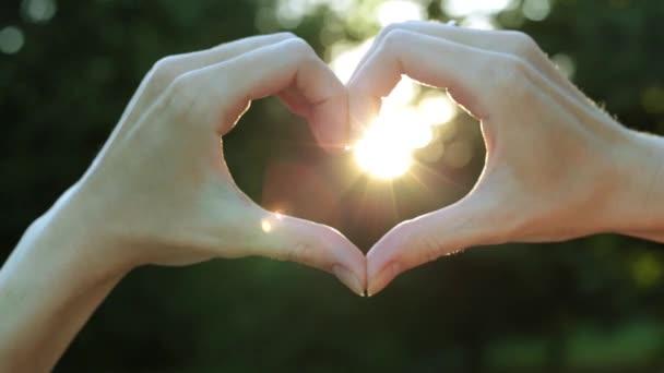 Női kéz a háttérben a nap a szív alakú. Szív alakú női ujjak.