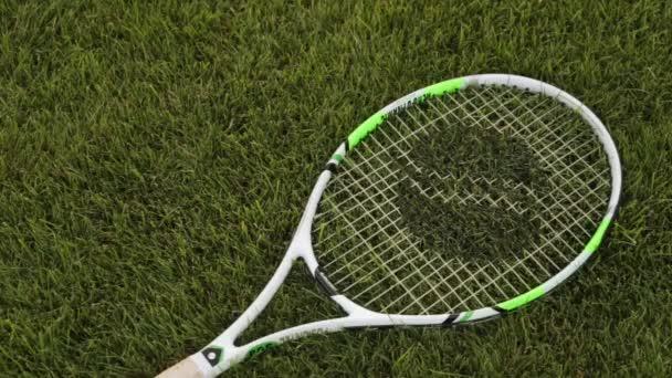 Tenisovou raketu a tenisový míček v trávě