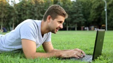 A man in the park is working on a laptop. Mobile office, freelancer.