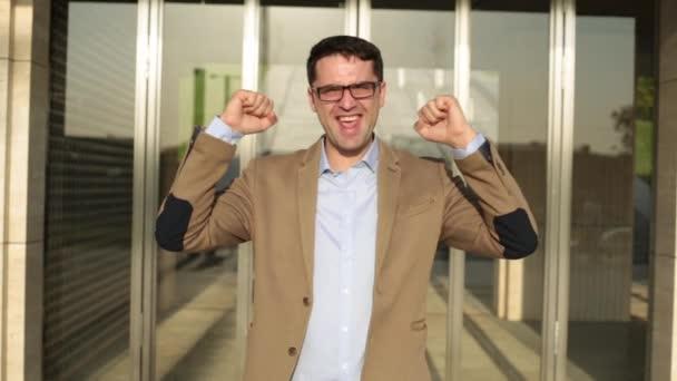 Muž podnikatel se raduje v úspěch. Radostné ruce nahoru.