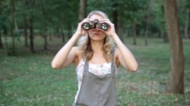 A woman in the forest looks through binoculars.