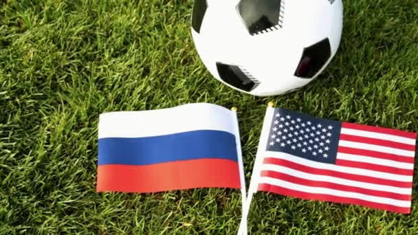Soccer ball and flags of Russia and the USA. Football, ball on the grass, World Cup.