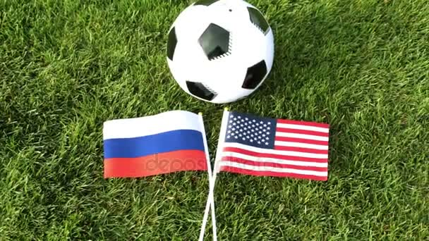 Soccer ball and flags of Russia and the United States. Football, ball on the grass, World Cup.