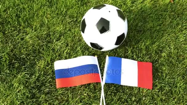 Soccer ball and flags of Russia and France. Football, ball on the grass, World Cup.