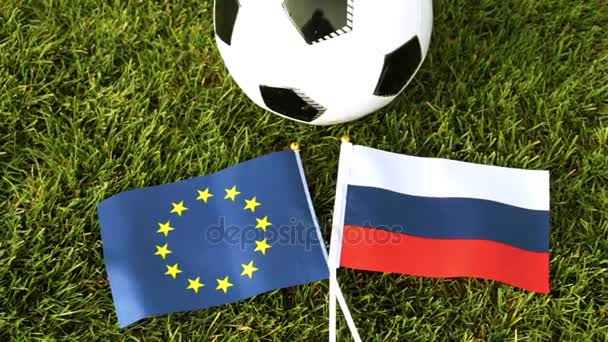 Fotbalový míč a vlajky Ruska a Evropské unie. Fotbalový míč v trávě, světový pohár