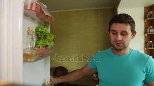 A férfi előveszi az ananász, a hűtőből. Az ember a konyhában megnyitja a hűtő.