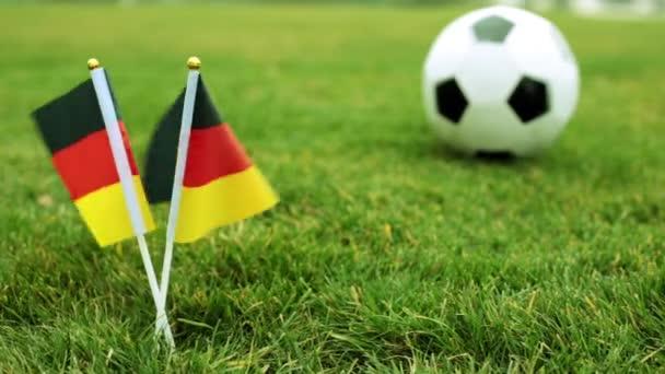 Német zászlók és a futball-labda, zöld fű.