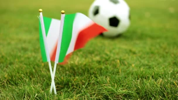 Italian flag on the background of a soccer ball. Italian flag and football ball on the grass