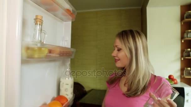 Egy nő húzza ki, és ital a tej, a hűtőből.