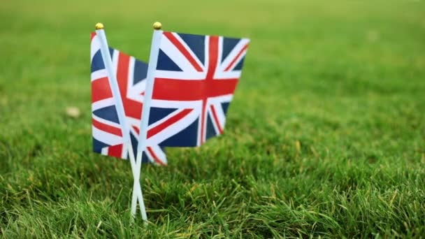 The flag of the United Kingdom flutters in the wind. Flag of Great Britain on the grass.