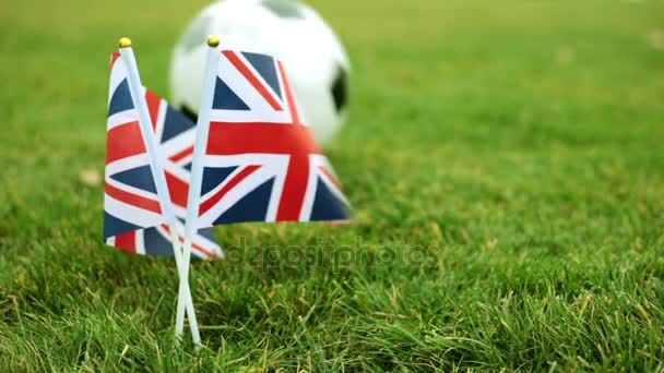 Flag of United Kingdom and a football ball. British flag and soccer ball on the grass.