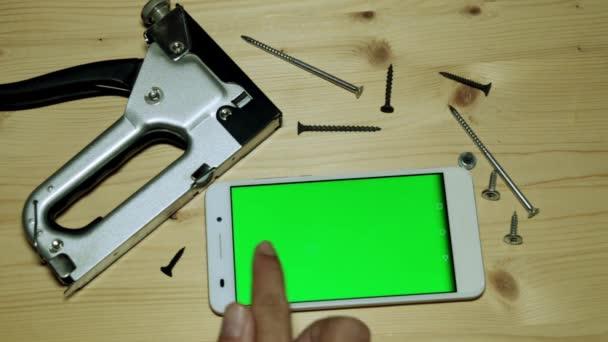 Smartphone s zeleným plátnem a sešívačka stavební. Telefonní a stavební nástroje.