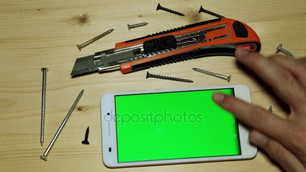 Stavební nůž a smartphone s zeleným plátnem pro svůj obsah.