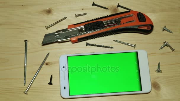 Smartphone s zeleným plátnem pro obsah a stavební nářadí.
