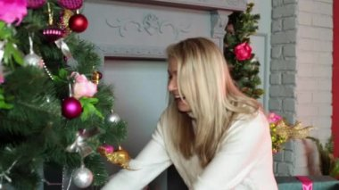 A woman is considering a gift next to a Christmas tree. Christmas, gifts, New Year.