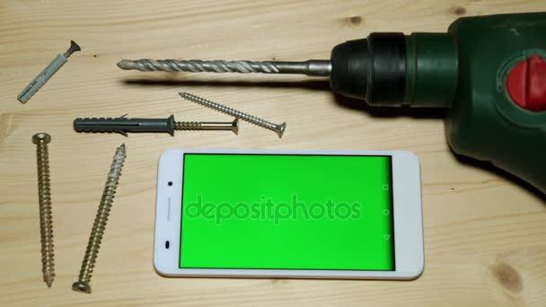 Stavební nástroje perforator a smartphone s zeleným plátnem.