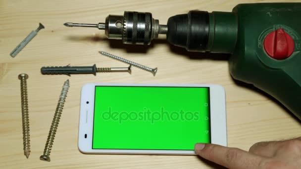 Stavební nástroje a smartphone s zeleným plátnem
