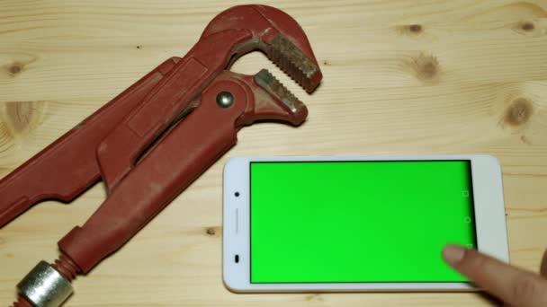Smartphone s zelený displej a instalatérské nástroje