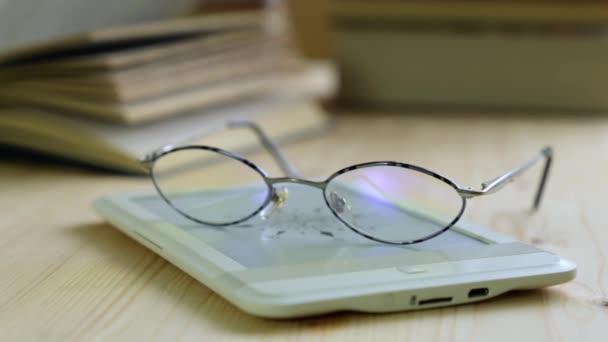 E-könyv, szemüveg és papír könyv.